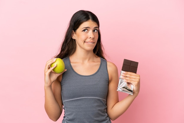 Young caucasian woman isolated on pink background having doubts while taking a chocolate tablet in one hand and an apple in the other