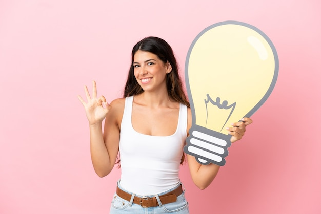 Young caucasian woman isolated on pink background holding a bulb icon and doing ok sign