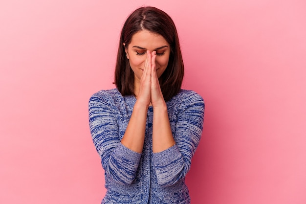 Young caucasian woman isolated on pink background holding hands in pray near mouth, feels confident. Premium Photo
