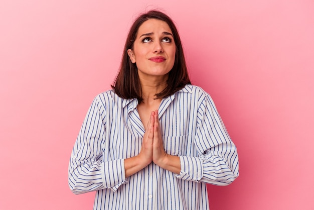 Young caucasian woman isolated on pink background holding hands in pray near mouth, feels confident.
