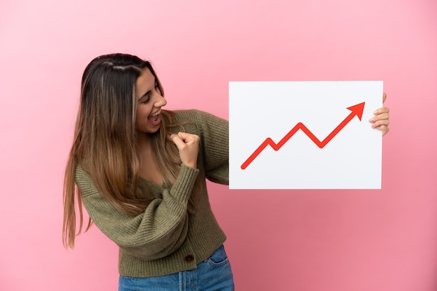 Young caucasian woman isolated on pink background holding a sign with a growing statistics arrow symbol and celebrating a victory
