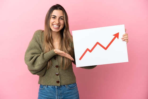 Young caucasian woman isolated on pink background holding a sign with a growing statistics arrow symbol and  pointing it