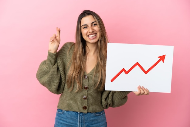 Young caucasian woman isolated on pink background holding a sign with a growing statistics arrow symbol with fingers crossing