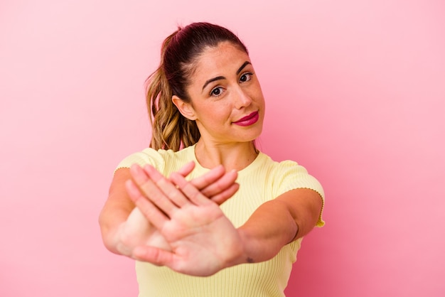 Young caucasian woman isolated on pink background hugs, smiling carefree and happy.