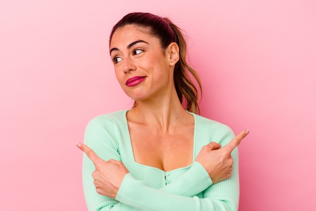 Young caucasian woman isolated on pink background keeping eyes opened to find a success opportunity.