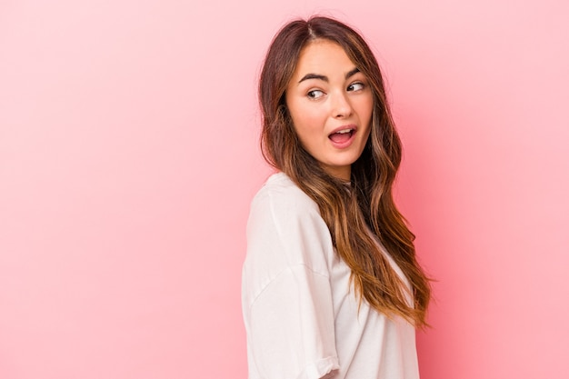 Young caucasian woman isolated on pink background looks aside smiling, cheerful and pleasant.