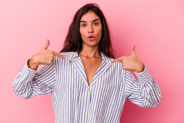 Young caucasian woman isolated on pink background points down with fingers, positive feeling.