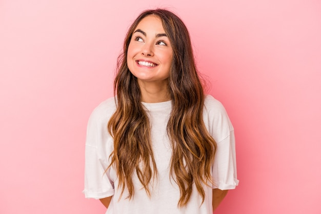 Young caucasian woman isolated on pink background relaxed and happy laughing, neck stretched showing teeth.