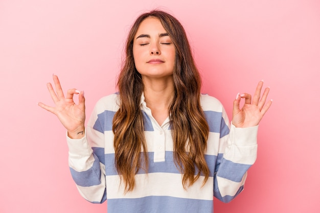 Young caucasian woman isolated on pink background relaxes after hard working day, she is performing yoga.