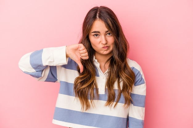 Young caucasian woman isolated on pink background showing thumb down, disappointment concept.