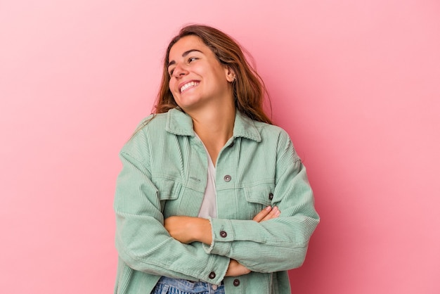 Young caucasian woman isolated on pink background  smiling confident with crossed arms.