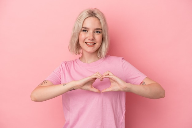 Young caucasian woman isolated on pink background smiling and showing a heart shape with hands.