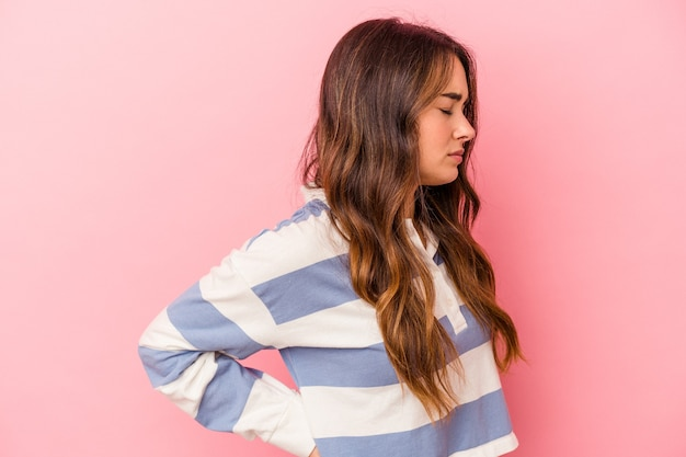 Young caucasian woman isolated on pink background suffering a back pain.