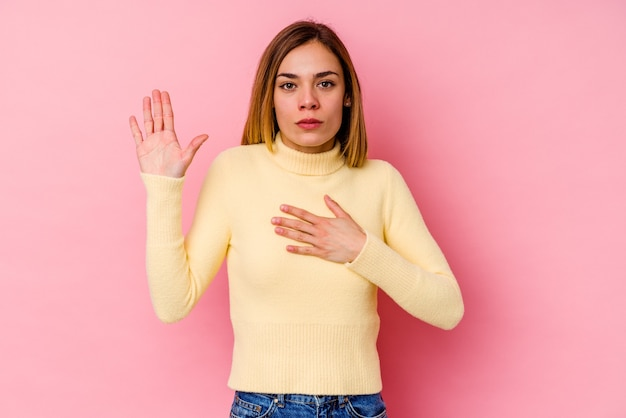 Young caucasian woman isolated on pink background taking an oath, putting hand on chest.