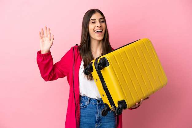 Young caucasian woman isolated on pink background in vacation with travel suitcase and saluting