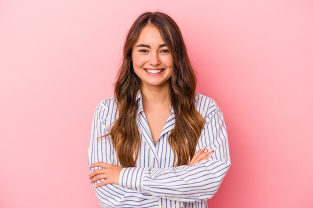 Young caucasian woman isolated on pink background who feels confident, crossing arms with determination.