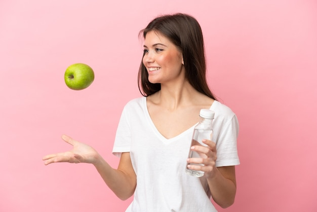 Young caucasian woman isolated on pink background with an apple and with a bottle of water