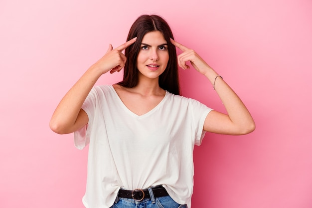 Young caucasian woman isolated on pink wall focused on a task, keeping forefingers pointing head
