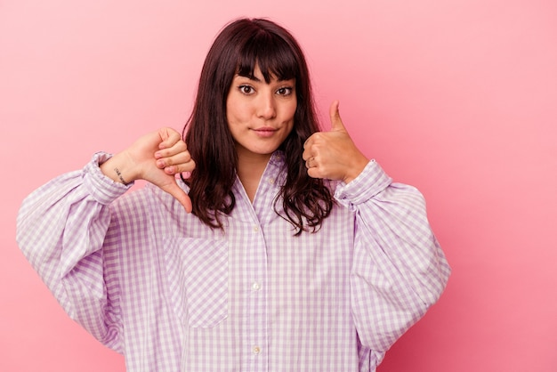 Young caucasian woman isolated on pink wall showing thumbs up and thumbs down, difficult choose concept