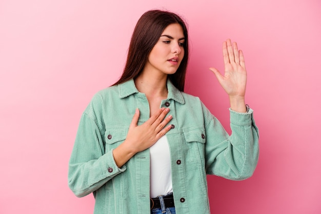 Young caucasian woman isolated on pink wall taking an oath, putting hand on chest