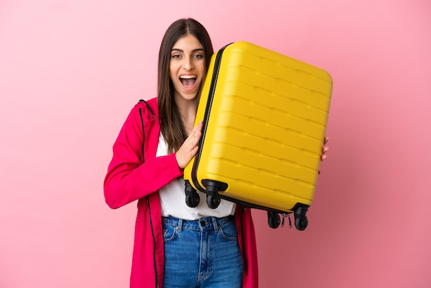 Young caucasian woman isolated on pink wall in vacation with travel suitcase and surprised