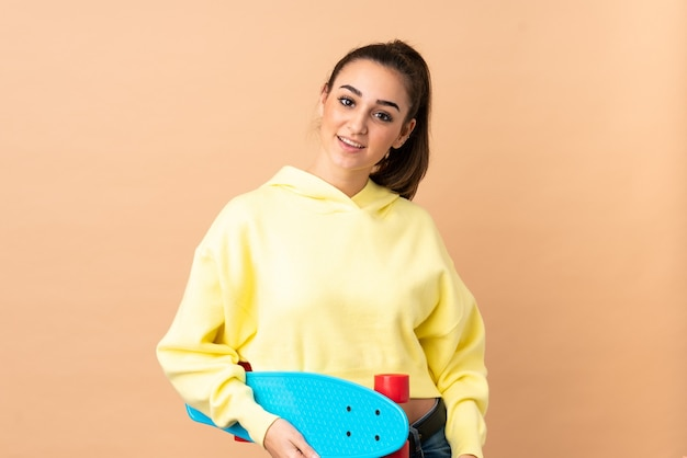 Young caucasian woman isolated on pink wall with a skate