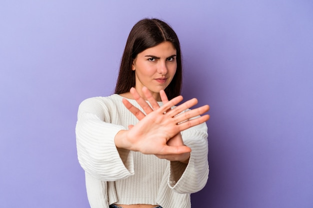 Young caucasian woman isolated on purple background doing a denial gesture