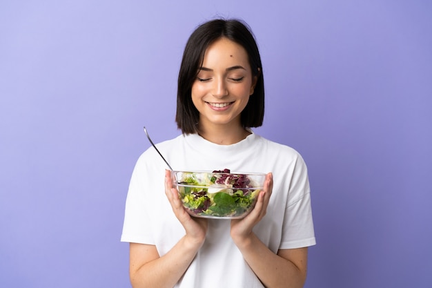 Young caucasian woman isolated on purple background holding a bowl of salad with happy expression
