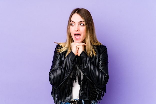 Young caucasian woman isolated on purple background praying for luck, amazed and opening mouth looking to front.
