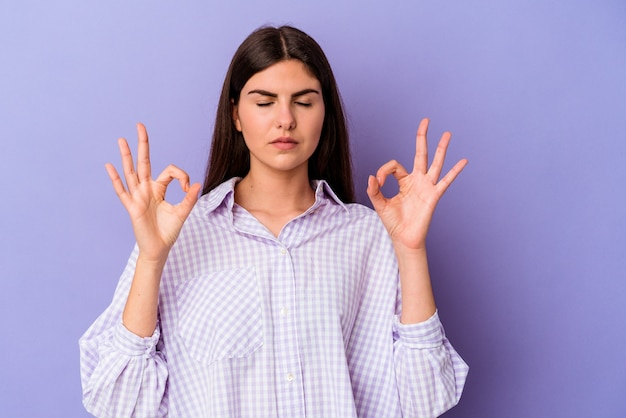 Young caucasian woman isolated on purple background relaxes after hard working day, she is performing yoga.
