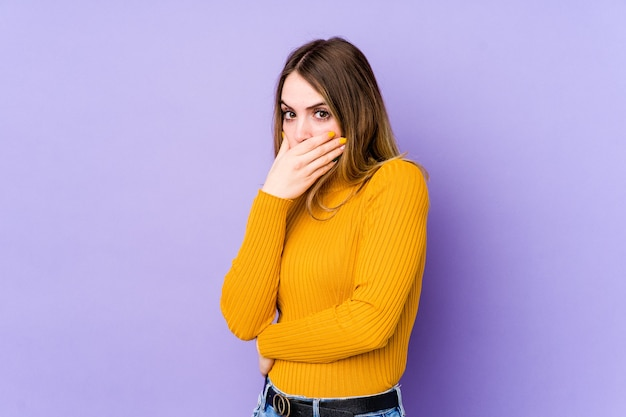 Young caucasian woman isolated on purple background scared and afraid.