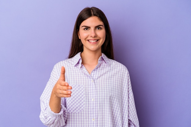 Young caucasian woman isolated on purple background stretching hand at camera in greeting gesture.