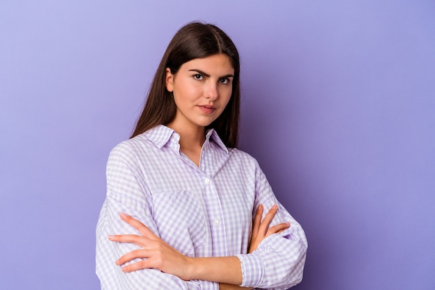 Young caucasian woman isolated on purple background suspicious, uncertain, examining you.