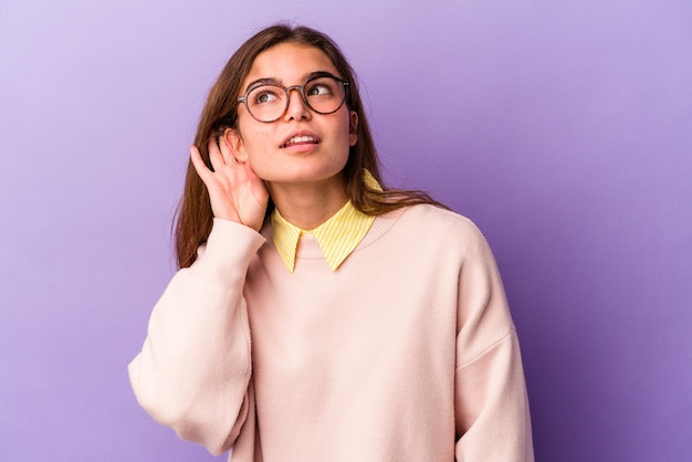 Young caucasian woman isolated on purple background trying to listening a gossip.
