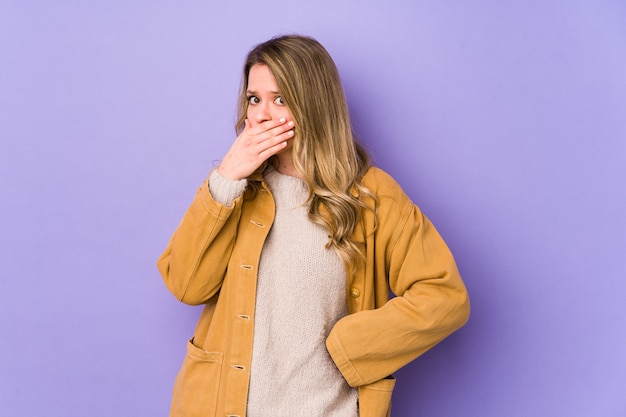 Young caucasian woman isolated on purple covering mouth with hands looking worried.