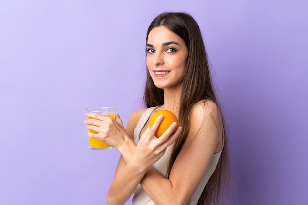 Young caucasian woman isolated on purple holding an orange and an orange juice