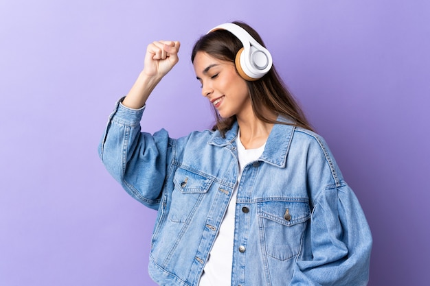 Young caucasian woman isolated on purple listening music and dancing