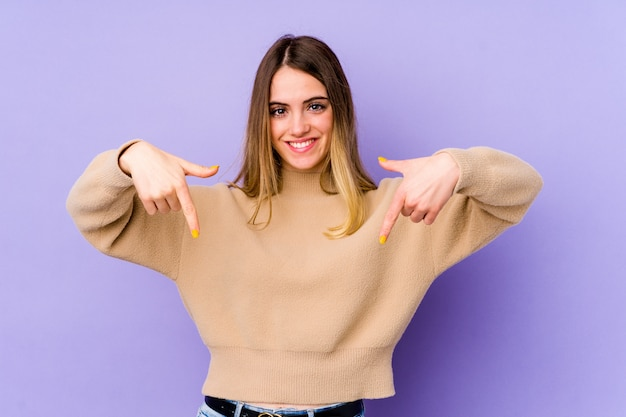 Young caucasian woman isolated on purple points down with fingers, positive feeling.