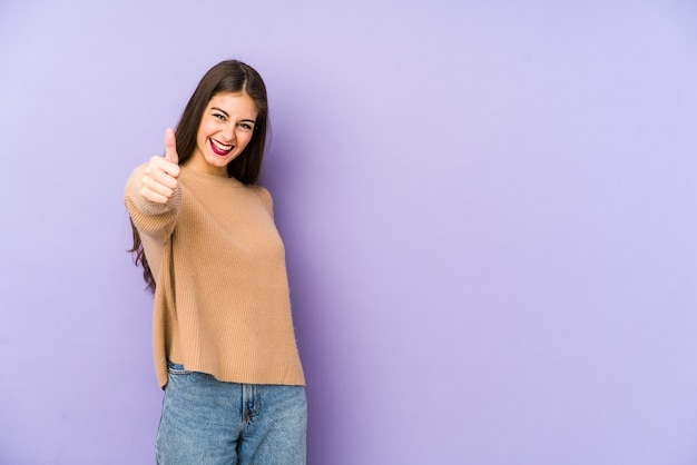 Young caucasian woman isolated on purple smiling and raising thumb up
