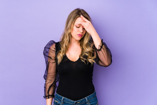 Young caucasian woman isolated on purple space having a head ache, touching front of the face.
