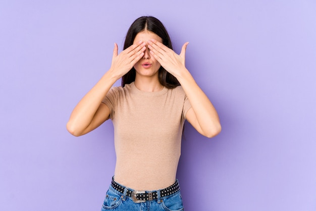 Young caucasian woman isolated on purple wall afraid covering eyes with hands.