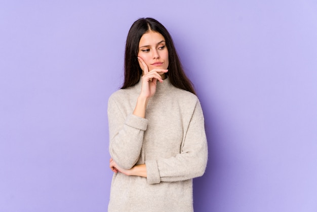 Young caucasian woman isolated on purple wall contemplating, planning a strategy, thinking about the way of a business.