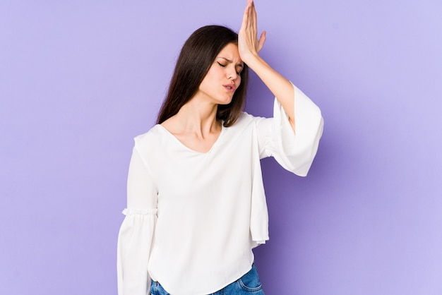 Young caucasian woman isolated on purple wall forgetting something, slapping forehead with palm and closing eyes.