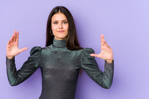 Young caucasian woman isolated on purple wall holding something little with forefingers, smiling and confident.