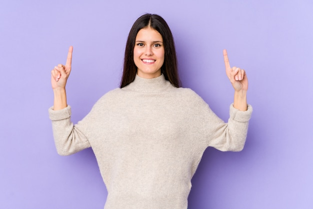 Young caucasian woman isolated on purple wall indicates with both fore fingers up showing a blank space.