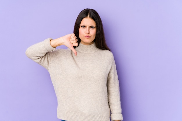 Young caucasian woman isolated on purple wall showing thumb down, disappointment concept.