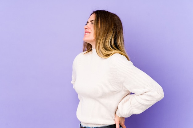 Young caucasian woman isolated on purple wall suffering a back pain.