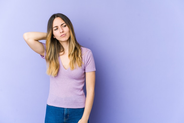 Young caucasian woman isolated on purple wall suffering neck pain due to sedentary lifestyle.