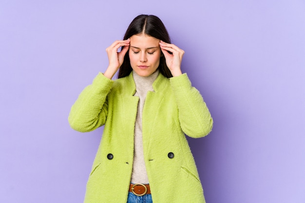 Young caucasian woman isolated on purple wall touching temples and having headache.