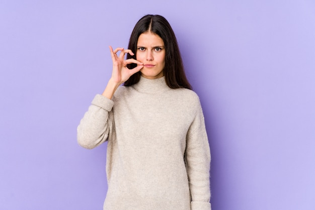Young caucasian woman isolated on purple wall with fingers on lips keeping a secret.